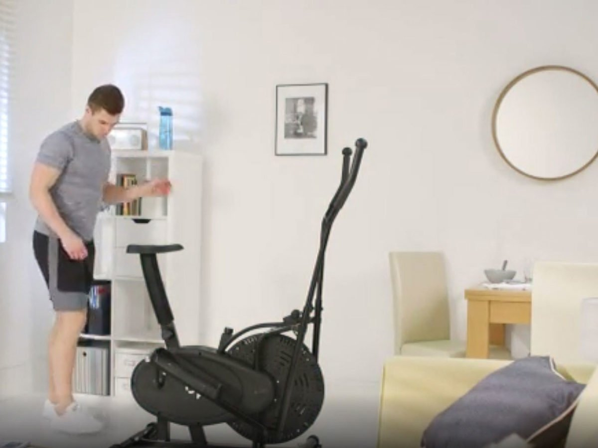 Man using the Opti 2-in-1 Air Cross Trainer and Exercise Bike in living room